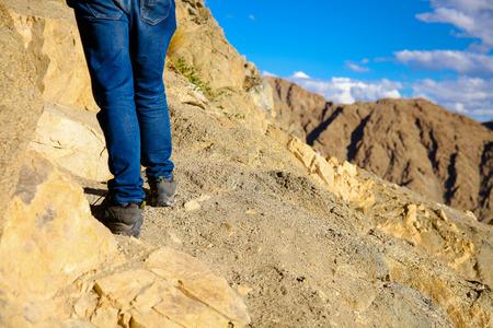 Close-up of traveler\'s feet walking uphill on mountain and sand dune over blue sky - travel, vacation,recreation and adventure concept
