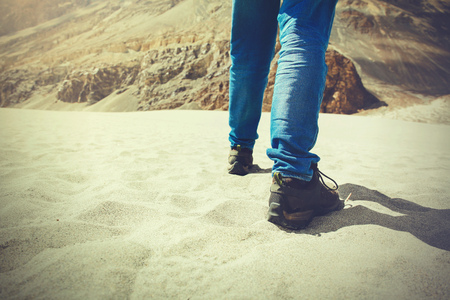 Traveler walking in the sand dune towards the hill - travel, vacation,recreation and adventure (Vintage tone).