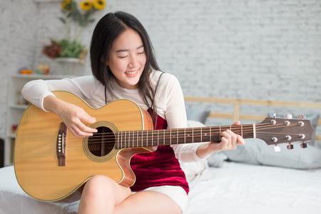 Foto de Cute and happy smiling Asian girl playing acoustic guitar in bedroom - Imagen libre de derechos