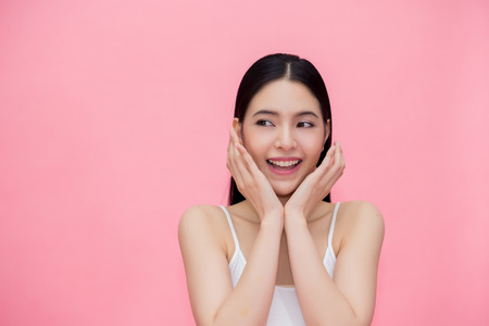 Photo for Excited and surprised smiling Asian 20s woman isolated over pink background - Royalty Free Image