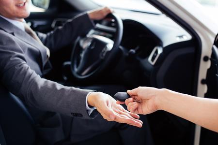 Photo pour Smiling and happy man receiving a car key from car dealer salesman - car rental and sales concept - image libre de droit