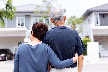 Foto de Happy senior couple from behind looking at front of house and car - Imagen libre de derechos