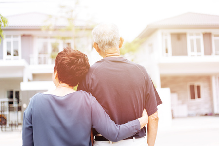 Foto de Happy senior couple from behind looking at front of house and car. Warm tone with sunlight - Imagen libre de derechos