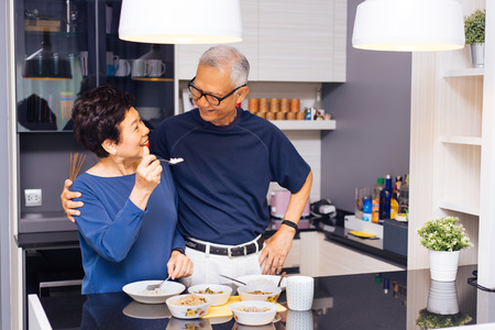 Foto de Senior Asian couple grandparents cooking together while woman is feeding food to man at the kitchen. Long lasting relationship concept - Imagen libre de derechos