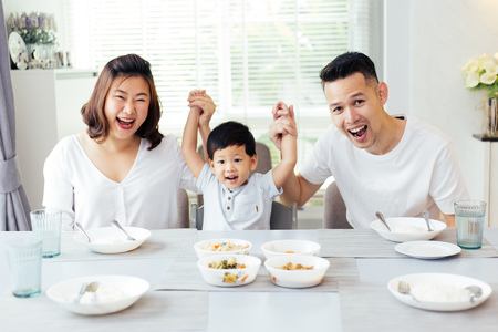 Photo pour Happy Asian family raising child's hands up and smiling while having a meal together - image libre de droit