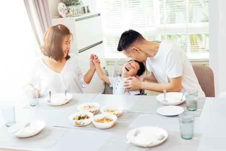 Foto de Happy Asian family of father, mother and son playing and laughing while having dinner - Imagen libre de derechos