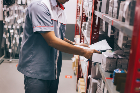 Foto de Male inventory worker on duty checking and inspecting stocks in warehouse or storehouse in control - Imagen libre de derechos