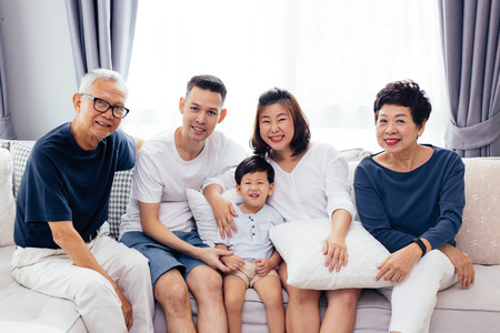 Foto de Happy Asian extended family sitting on sofa together, posing for group photos - Imagen libre de derechos