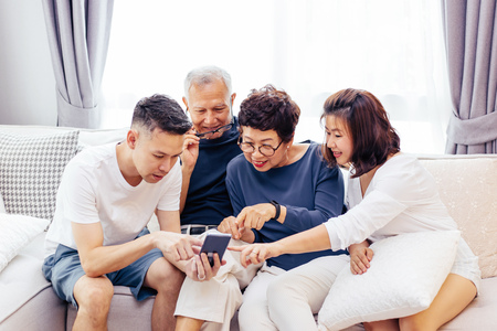 Photo pour Asian family with adult children and senior parents using a mobile phone and relaxing on a sofa at home together - image libre de droit