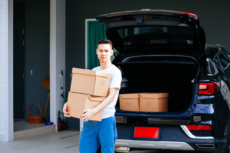 Photo pour Mature Asian man carrying cardboard boxes from car trunk at new home - image libre de droit