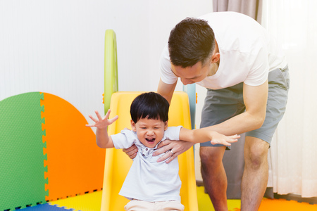 Photo pour Asian father accompanying child on the playground slider at home. Happy family with toys - image libre de droit