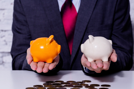 Foto de Businessman making a comparison and difference between each money piggy bank - finance issue comparison concept - Imagen libre de derechos