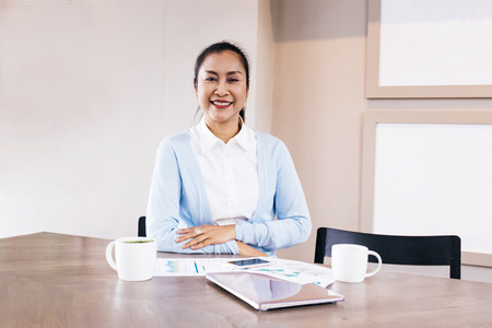 Foto de South East Asian beautiful middle aged business woman sitting in cafe with coffee cups and phone and laptop - Imagen libre de derechos