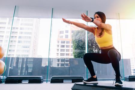 Foto de Side view of young attractive Asian fitness woman in sportswear doing deep squat at gym - Imagen libre de derechos