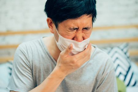 Photo pour Young Asian man coughing and suffering in medical mask inside home bedroom - illness and fever concept - image libre de droit