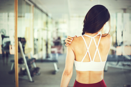 Photo for Close up of young muscular and active Asian female sportswoman having shoulder strain during indoors workout gym - Royalty Free Image