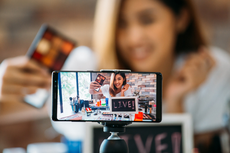 Photo for Happy young attractive Asian ethnic model filming vlog on mobile phone on tripod and showing eyeshadows at table with cosmetics - Royalty Free Image