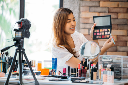 Photo for Pretty Asian woman recording makeup tutorial video about cosmetics with mobile phone on tripod. - Royalty Free Image