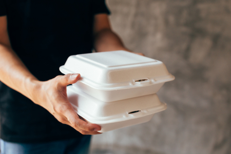 Foto de Close-up of delivery man handing a slack of foam lunch box - Foam box is toxic plastic waste. Used for recycling and environment saving concept - Imagen libre de derechos