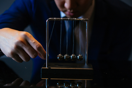 Photo for Unrecognizable businessman pulling small metal ball of Newton cradle and observing momentum over glass tabletop - Royalty Free Image