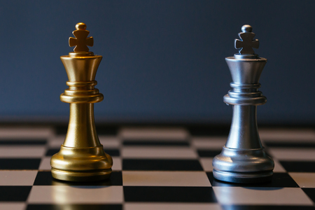 Foto de Close up shot of golden and silver chess kings placed against each other on chessboard - Imagen libre de derechos