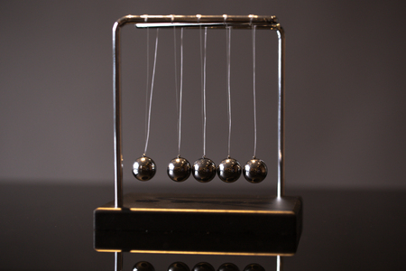 Foto de Closeup metal Newton cradle placed on gray background as representation of momentum concept - Imagen libre de derechos