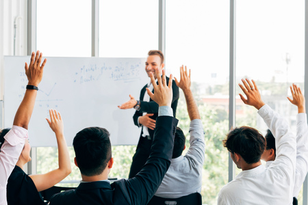 Foto de Many business people participants raising up their hand in business seminar conference event inside corporate company office with speaker in front - Imagen libre de derechos