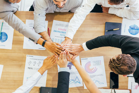 Photo pour Crop coworking business people stacking hands above wooden desk with paper documents - image libre de droit