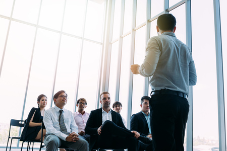 Photo for From below of businessman standing in front of colleagues in light sunny room and doing presentation - Royalty Free Image