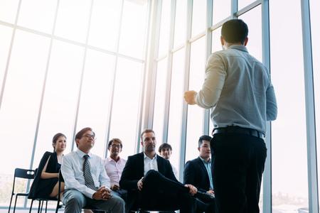 Foto de From below of businessman standing in front of colleagues in light sunny room and doing presentation - Imagen libre de derechos
