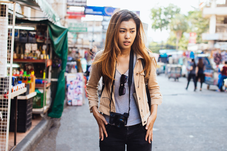 Foto de Young confused Asian woman checking pockets of jeans finding loss of stuff while traveling in city - Imagen libre de derechos