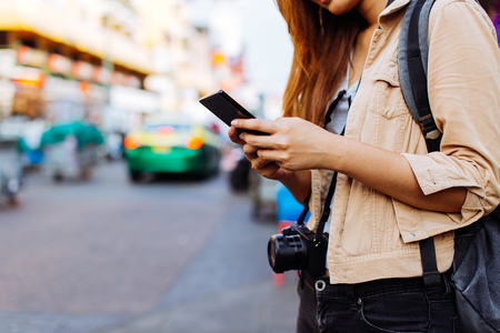 Young Asian female tourist woman using a mobile phone in Bangkok, Thailand. Calling a cab or finding information during traveling concept
