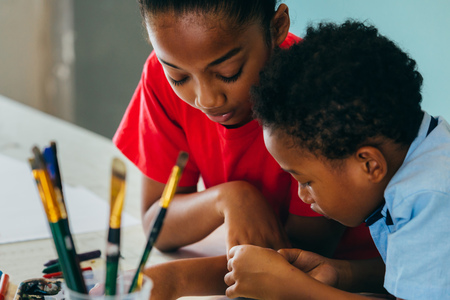 Foto de Closeup of elementary African American kids creatively drawing and painting with brushes and crayon - children creative education concept - Imagen libre de derechos