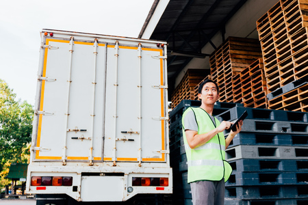 Foto de Young Asian male logistic warehouse distribution business entrepreneur using tablet. He surrounded by plenty of pallets and truck in shipping cargo. - Imagen libre de derechos