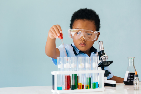 Photo pour Serious African American boy in protective goggles using pipette while trying to learn how to mix colorful chemicals in laboratory - image libre de droit
