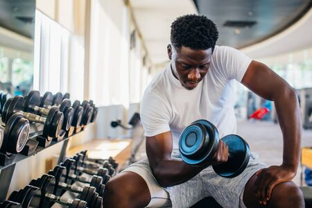 Foto de Young African American man sitting and lifting a dumbbell close to the rack at gym. Male weight training person doing a biceps curl in fitness center - Imagen libre de derechos