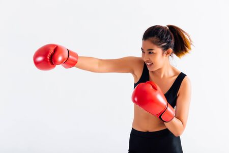 Foto de Portrait of a young smiling female boxer punching on white isolated background with copy space. Asian woman doing boxing exercise with happy look. - Imagen libre de derechos