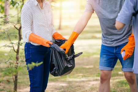 Photo for Cropped young teenage male and female group of volunteers with gloves collecting garbage waste into trash bag in green park. Environmental friendly and litter collection concept - Royalty Free Image