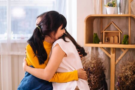 Foto de Face of smiling Asian teenage daughter and Asian middle-aged mother hugging with happy warm expression and tenderness in indoor living room at home. They have good relationship together. - Imagen libre de derechos
