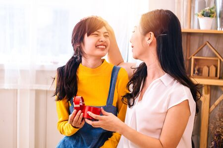 Foto de Asian middle-aged mother touching Smiling happy Asian teenage daughter in indoor living room at home. Mum holds and opens a present gift. - Imagen libre de derechos