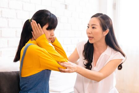 Photo for Argument between annoyed Asian teenage daughter and upset middle aged mother. The child covering ears while mum arguing. Bad, unhealthy, toxic family relationship concept - Royalty Free Image