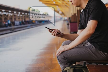 Young male tourist backpacker use a phone and wait for public transportation inside train platform - receiving train arrival push notification notice