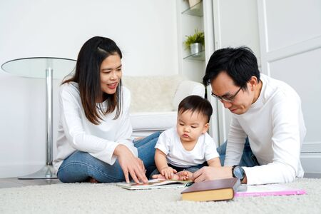 Photo pour Happy modern Asian parents sitting on floor with cute infant boy and reading fairy tale while enjoying time together at home - image libre de droit