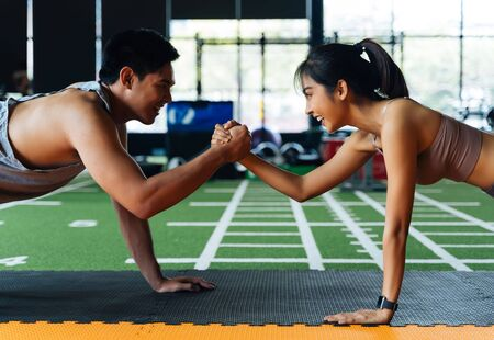 Foto de Healthy smiling couple of man and woman giving high five to each other while pushing up in the fitness gym. Asian sporty people working out together. Teamwork and achievement concept - Imagen libre de derechos
