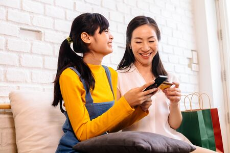 Photo for Happy smiling Asian woman and daughter in casual outfit browsing smartphone and using credit card while sitting on sofa with shopping bags - Royalty Free Image