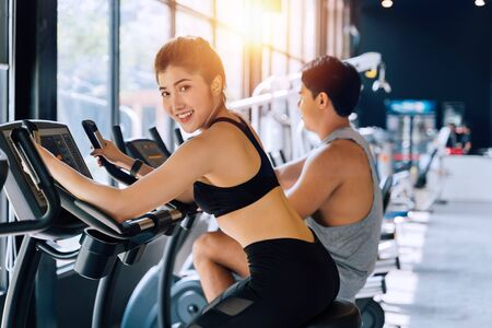 Photo pour Attractive Asian fitness woman riding on the spinning bike at the gym and looking at camera with copy space. Healthy and weight loss lifestyle - image libre de droit