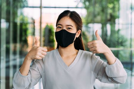 Photo pour Young optimistic Asian female student giving thumbs up gesture. Shes wearing a protective mask (PPE) to avoid air pollution or Corona Virus pandemic for safety. - image libre de droit