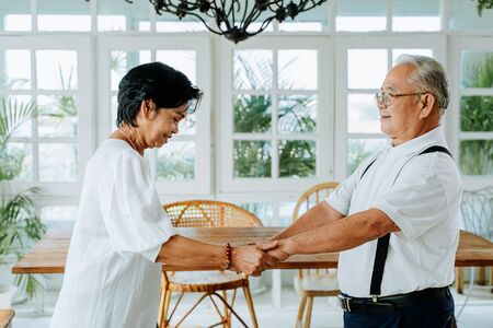 Happy old senior couple dancing and smiling in dinner room. Asian active elderly husband and wife holding hand and ejoying leisure retirement lifestyle at home
