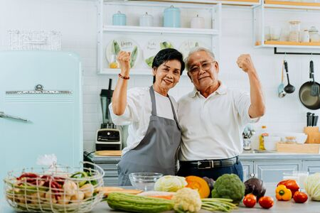 Photo pour Senior Asian married couple cooking food at kitchen home. Elderly 70s man and woman looking at camera while preparing ingredients at kitchen counter together. - image libre de droit