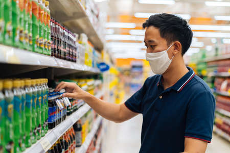 Foto für Young adult Asian man wearing a face mask while shopping with cart trolley in grocery supermarket store. Hes choosing to buy products in the grocery store during Covid 19 crisis in Thailand - Lizenzfreies Bild